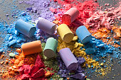 Colorful chalks with broken pastel particles on a blackboard.
