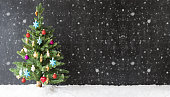 Colorful Christmas Tree On Snow And Snowflakes. Black Background With Copy Space For Advertisement