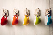 Colorful coffee cups on hooks