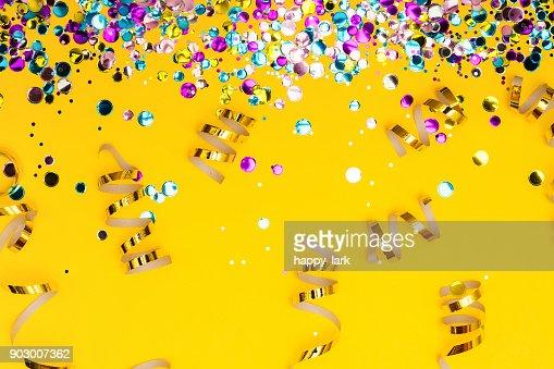 Colorido confeti y serpentinas doradas en espiral sobre fondo amarillo : Foto de stock