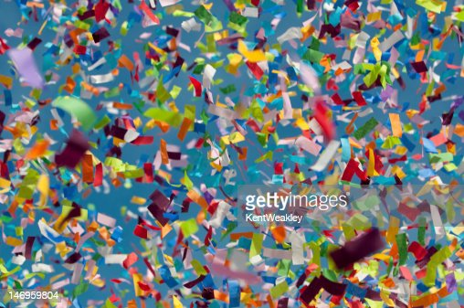 Colorful confetti in foreground with blue sky behind : Stock Photo