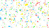 Red, blue, green and yellow confetti falling in front of a white background