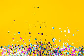 Colorful confetti on yellow background. Holiday frame. Copy space