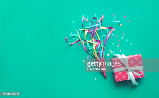 Colorido confeti, serpentinas y regalo caja en color verde : Foto de stock
