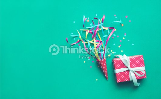 Colorful confetti,streamers and gift box on green color : Stock Photo