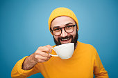 Cheerful bright hipster in hat and sweater enjoying cup of freshly made coffee.