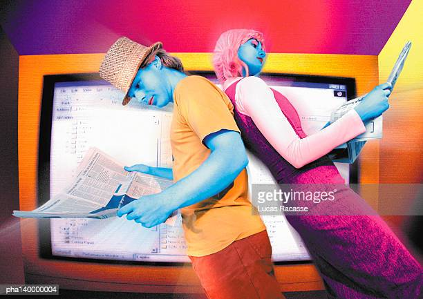 Colorful couple standing back to back, reading in front of monitor, digital composite.