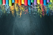 Colorful crayons on the blackboard, drawing. Back to school background. Selective focus. Background with copy space.