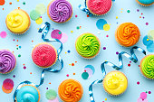 Colorful cupcake party background on blue