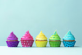 Row of colorful cupcakes on blue