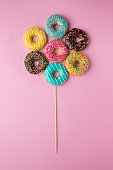 Colorful donuts on pink background. Colorful creative concept.