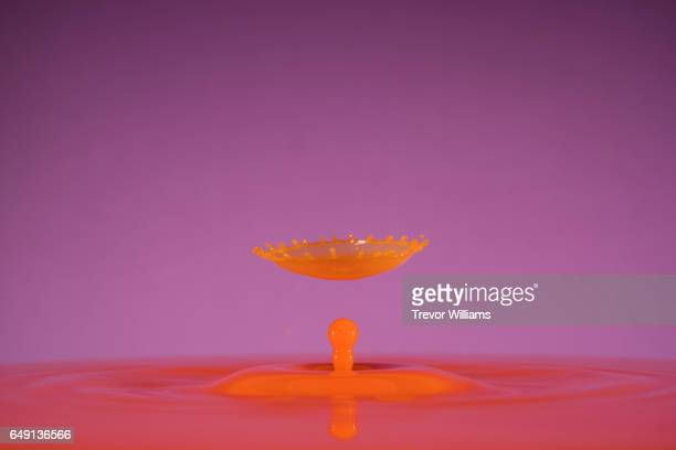 Colorful droplet splashing into itself against bright background