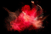 Colorful dust particle explosion resembling blood or a pyrotechnic effect over black. Closeup of a color explosion isolated on black