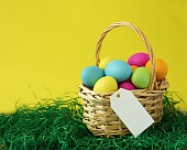 Colorful Easter eggs basket on green grass greeting card with white blank paper label tag for message and copy space on yellow background.