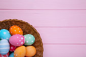 Colorful easter eggs in basket on pink background