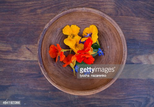Colorful edible flowers in clay bowl on wooden background : Stock Photo