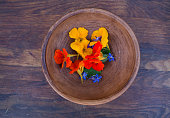 Colorful edible flowers in clay bowl on wooden background. Bright nasturtium flowers with leaves and borage. Healthy organic food.