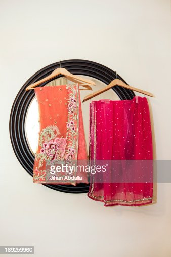 Colorful fabrics hanging by mirror