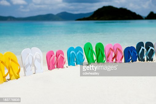 colorful family sandals in white sand on a Caribbean beach