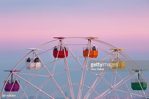 Colorful ferris wheel in the Tibidabo amusement park mountain with the Barcelona city view and the pink sunset sky.