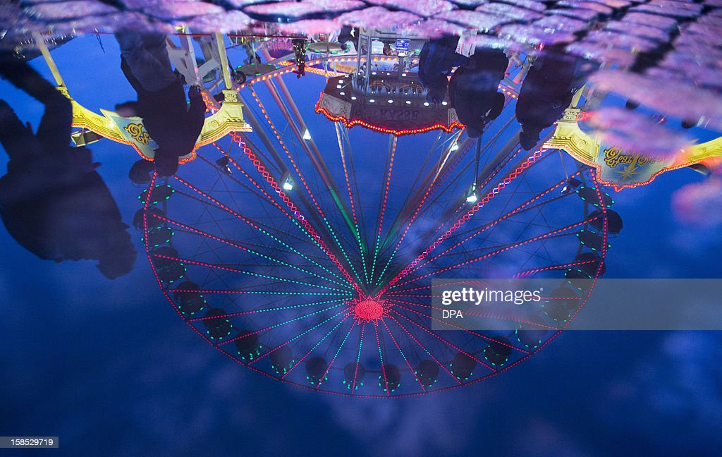 A colorful Ferris Wheel is reflected in a puddle at the Christmas Market in Schwerin, eastern Germany, on December 18, 2012. The Christmas Market in Schwerin remains open until December 30, 2012.