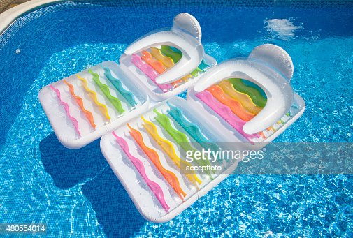 Colorful floating air mattresses in swimming pool at summertime : Stock Photo