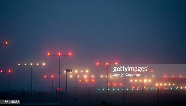 Colorful fogbound landing lights guide airplanes