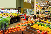 Colorful fresh fruits and vegetables are displayed in produce section of local grocery store or supermarket. Rows of tomatoes, peppers, potatoes, bananas, apples, and other natural organic produce is