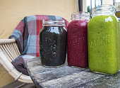 A close up photo of three jars outdoors with colorful smoothies.