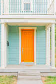 Freshly painted home with tangerine door and baby blue siding