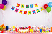 colorful garlands, streamer, party hats and confetti. festive decoration background with sample