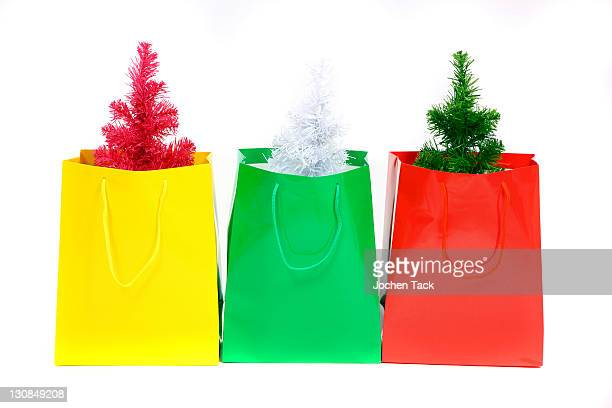 Colorful gift bags with small plastic Christmas trees, Christmas shopping