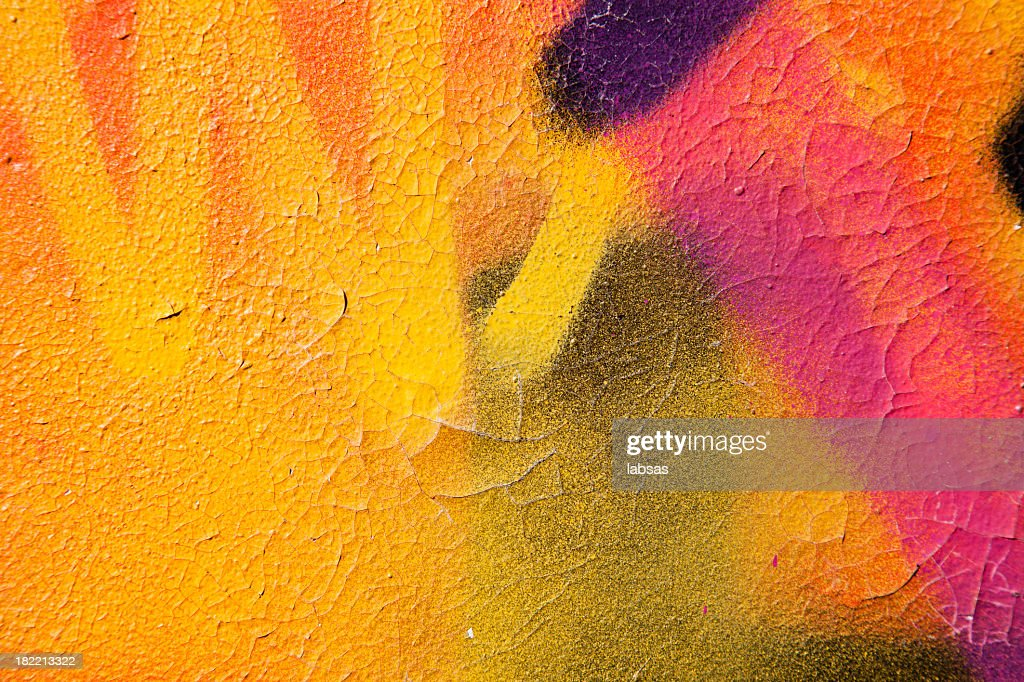 Colorful graffiti over a cracked surface : Stock Photo