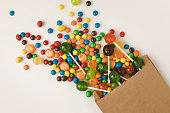 close-up view of colorful tasty candies in paper bag on white