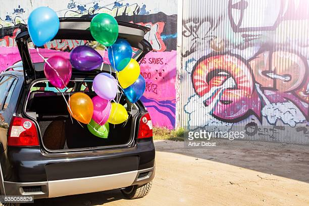 Colorful helium balloons flying away from a car trunk with colorful graffitis on the background street