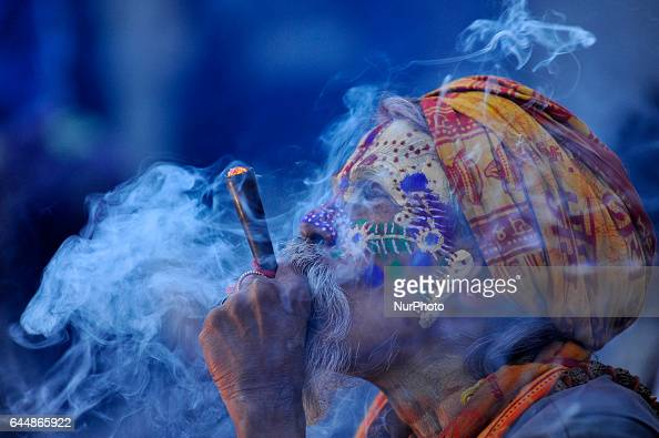 A colorful Hindu Sadhu or Holy Man smokes marijuana at the premises of Pashupatinath Temple during the celebration of Maha Shivaratri Festival at...