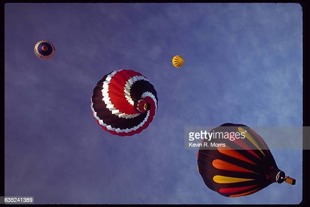 Colorful hot air balloons float up in blue sky in the Teton Valley Hot Air Balloon Festival in Driggs Idaho USA