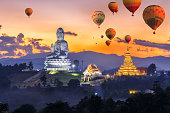 Colorful hot air balloons flying over Wat Huay Pla Kang, Chinese temple in Chiang Rai Province, Thailand