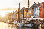 Colorful houses in Copenhagen old town at sunset, with boats and ships in the canal in front of them.