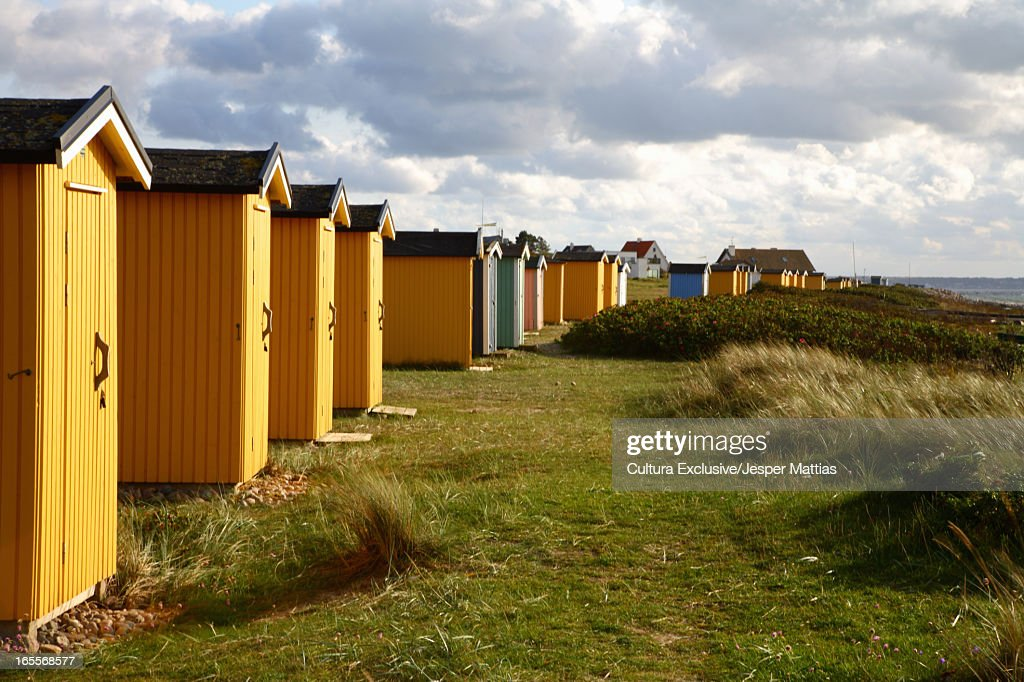 Colorful huts in grassy field : Stock Photo