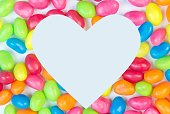 Colorful jelly bean background with white heart shaped space for text copy space