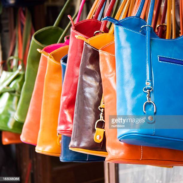 Colorful large hand bags hanging from rack