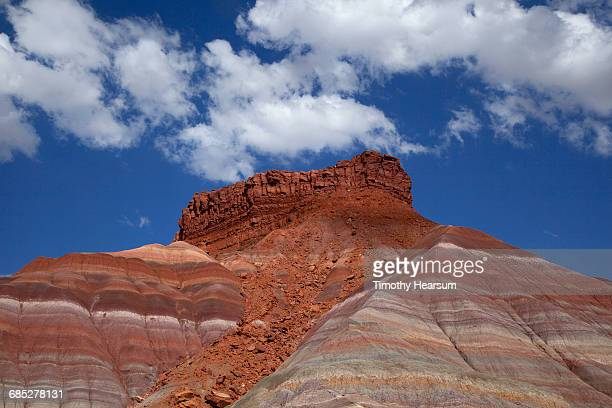 Colorful layered rock formations; sky beyond