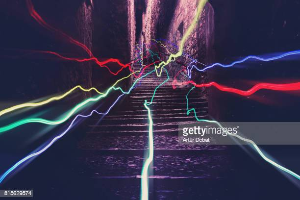 Colorful light trails with nice vanishing point and motion at night in the stairs of the old medieval streets of the Girona city.
