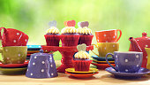 Colorful Mad Hatter style tea party with cupcakes and rainbow colored polka dot cups and saucers, with bokeh garden background and lens flare, with copy space.