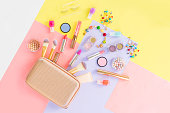 Colorful make up products with golden pursue pop art flat lay scene
