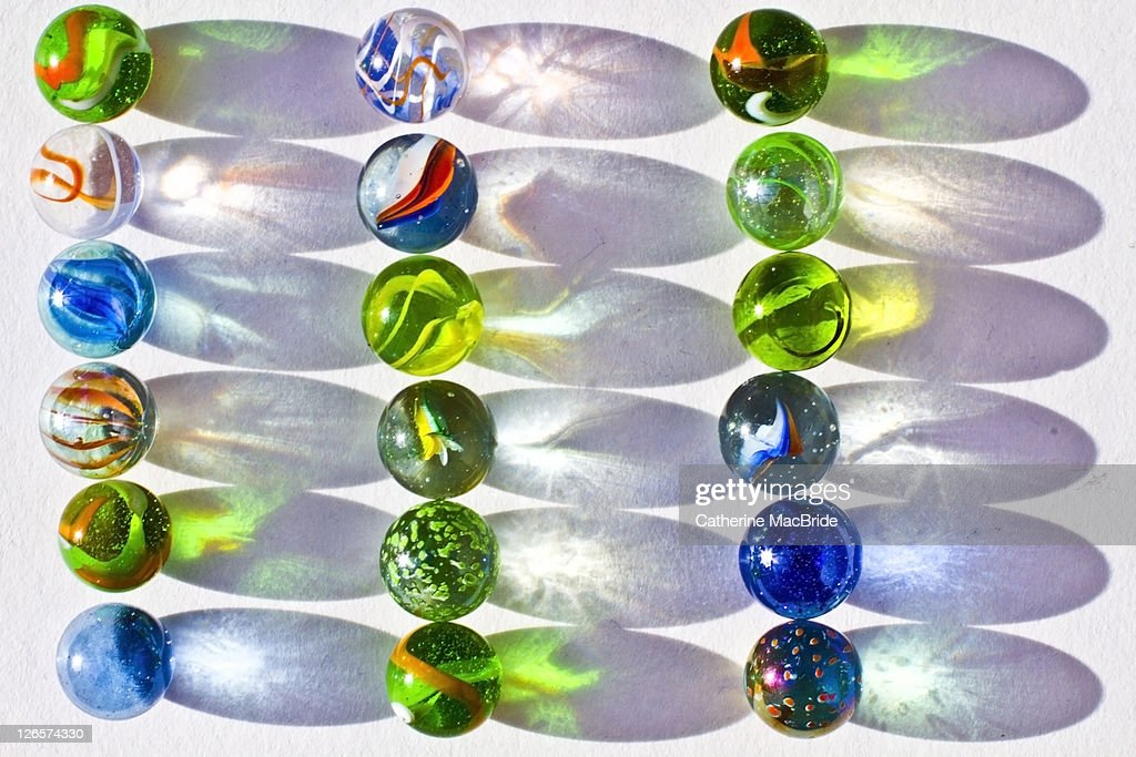 Colorful marbles and shadows : Stock Photo