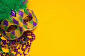 A festive, colorful mardi gras or carnivale mask on a yellow background.  Venetian mask.