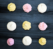 Many sweet zephyrs on wood background. Trendy top view dessert image.