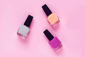 Pastel colors nail polishes on pink colored background. Beauty blogger concept